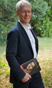 Photo de Philippe Nicolas dans un jardin avec son roman Les Âmes peintes en main.